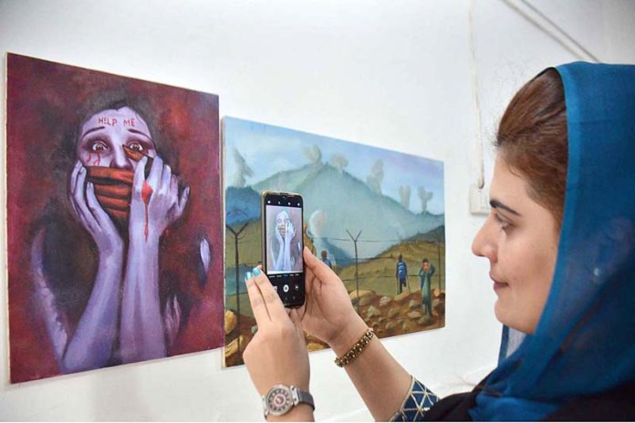 PESHAWAR: November 04 - Female visitor capturing displayed painting during Art & Painting Exhibition and Competition organized by Commissionerate for Afghan Refugees KP at Art and Design University. APP Photo by Shaheryar Anjum