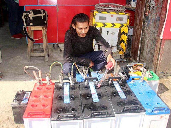 LAHORE: November 04 - A worker charging batteries in his shop. APP photo by Tabasam Naveed