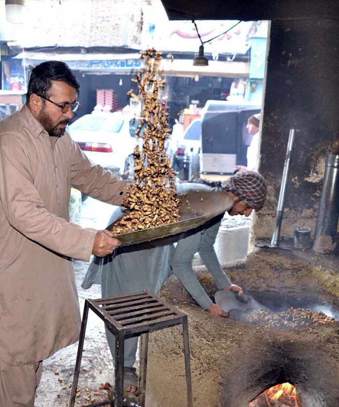 Vendors roasting peanuts in their shop at Masjid Road