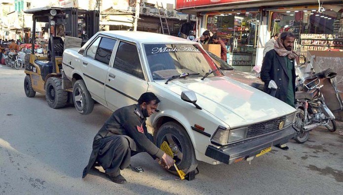 Traffic police official locking the wheel of vehicle over violation of traffic rules at Liaquat Bazaar