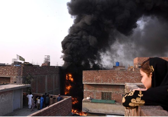 LAHORE: November 02 - People witnessing the fire erupted at scrap yard place at Badami Baagh. APP photo by Mustafa Lashari