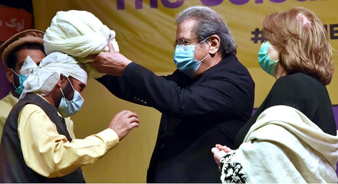 "ISLAMABAD: November 06 – Federal Minister for Education and Professional Training Mr. Shafqat Mahmood confers a turban to an artist during the opening ceremony of Folk Festival of Pakistan ""LOK MELA"" at Lok Virsa Shakarparian. APP photo by Irfan Mahmood"