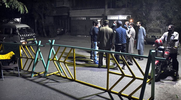 LAHORE: November 10 - Residents standing near the barrier as smart lockdown imposed due to several cases of COVID-19 in different areas of the city. APP Photo by Mustafa Lashari