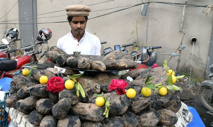A vendor displaying roasted sweet potatoes to attract the customers at his roadside setup