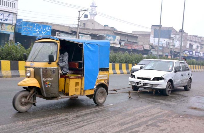 A rickshaw towing an out-of-order car on the way towards workshop at Sheikhupura Road
