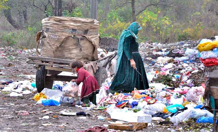 A gypsy woman along with her daughter searching valuables from heap of garbage in Federal Capital