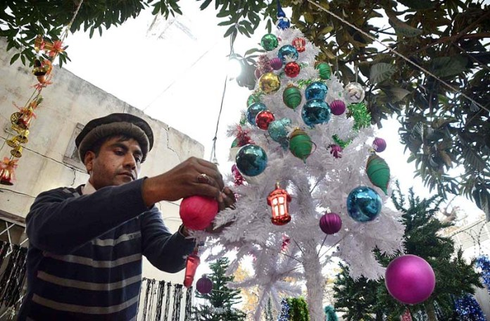 Christian decorating Christmas Tree on his stall at St. John Cathedral Church ahead of Christmas celebrations