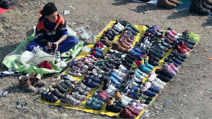 A young vendor displaying second hand shoes to attract customers at Kuri Road