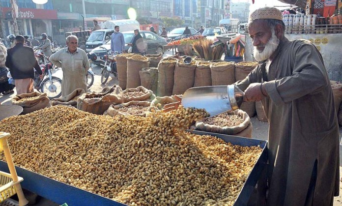 A vendor displaying and arranging peanuts to attract the customers at his shop
