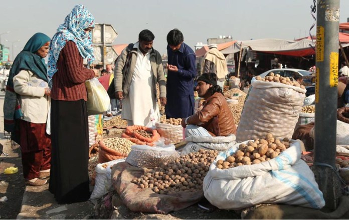 Customers purchasing dry fruits from a vendor at Pirwahdai