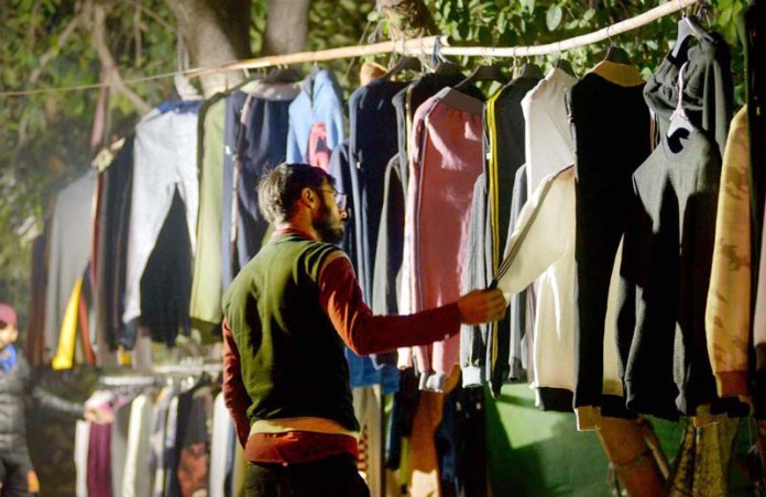 Youngster choosing warm clothes from roadside vendor at Karachi Company in Federal Capital