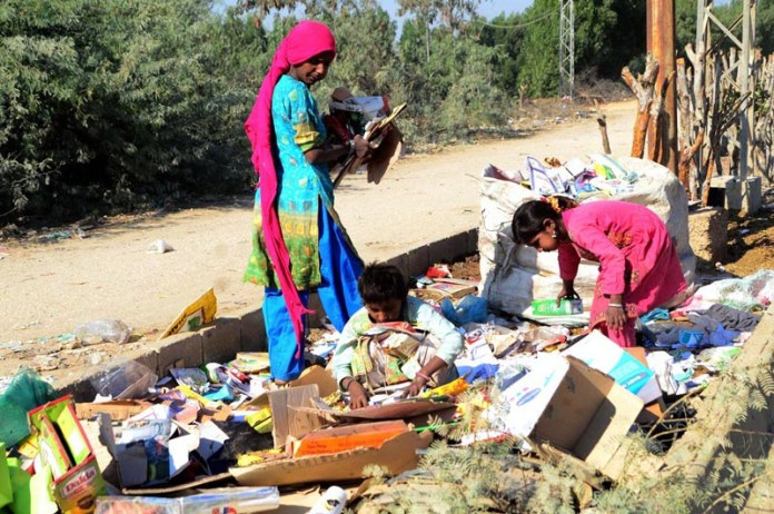 Gypsy children searching valuable items from garbage at Latifabad