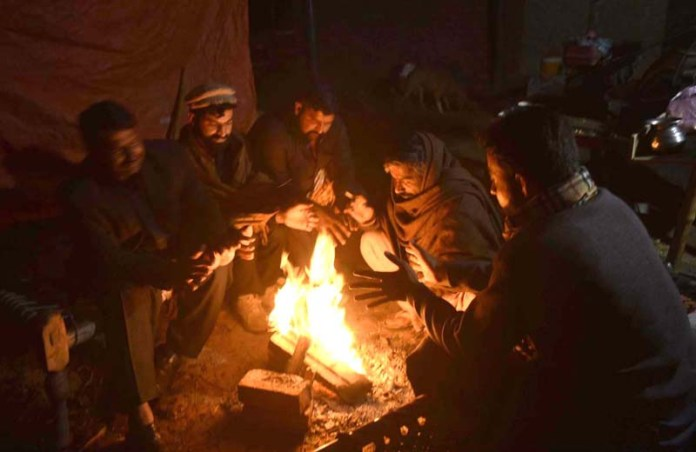 People sitting around fire to keep them warm during chilled weather in the city