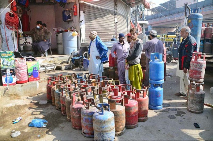 People waiting for their turn for filling LPG gas cylinders due to low pressure of gas at Makki Shah Road