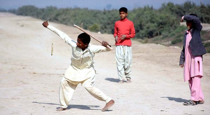 Children playing traditional game in front of their makeshift houses