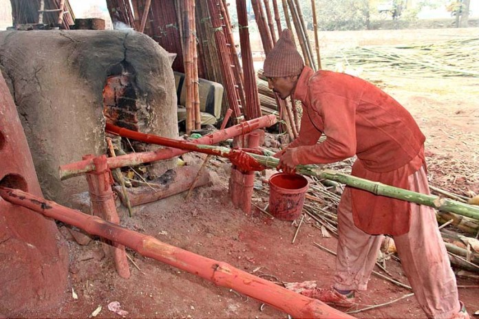 A worker busy in straightening bamboo at his workplace