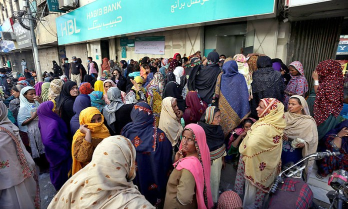 Large number of deserving people waiting for their turn outside a bank to withdraw cash under Ehsaas Cash Program without following the SOPs of corona virus