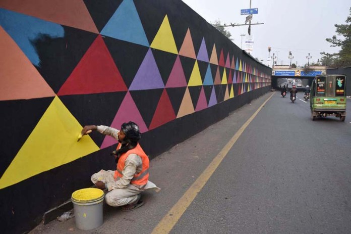Labourers busy in paint the different designs on the wall of underpass at Canal Road for beautification in the Provincial Capital