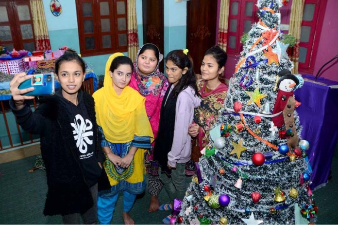 Christian girls taking selfie with Christmas tree after decorating Christmas Tree at St. Pual Church in connection with Christmas celebrations