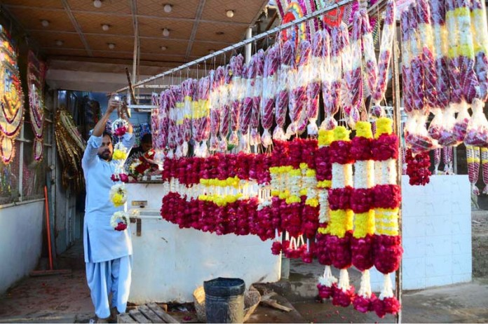 A vendor arranging flowers to attract the customers at his roadside setup