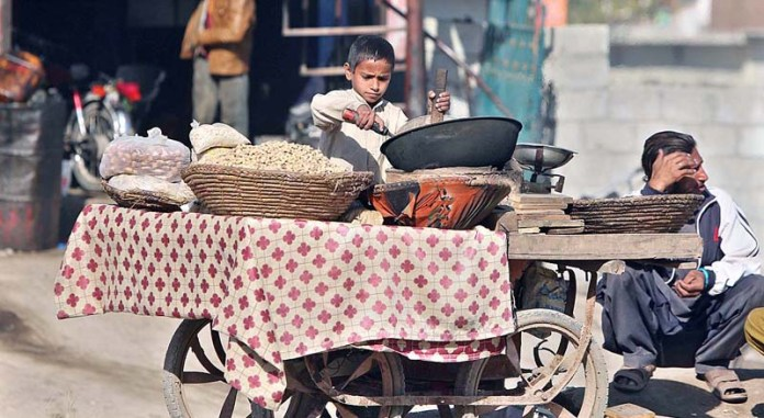 A young vendor busy in roasting grain at his roadside setup