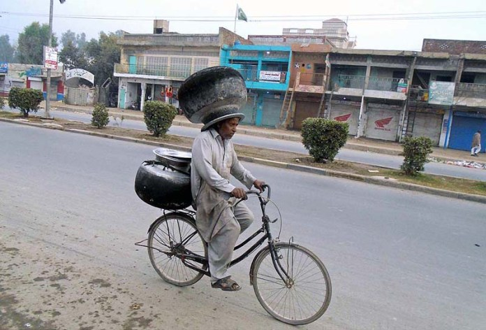 A person on the way on his bicycle while carrying cauldron on his head on the way at Sargodha Road