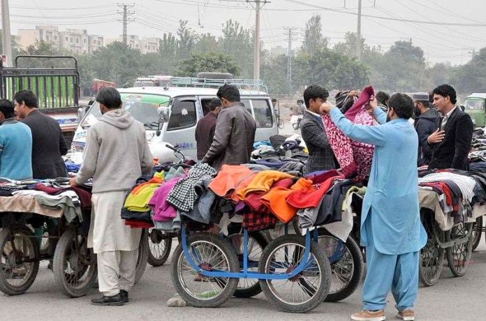 People purchasing warm clothes on his push cart at roadside setup