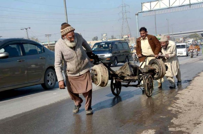 An elderly labourer pulling handcart loaded with vehicle spear part at Ring Road