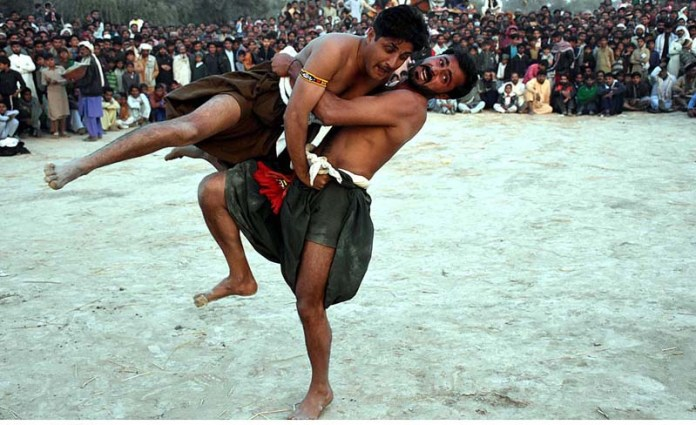 Wrestlers in action during traditional wrestling (Mulakhara) in front of Peer Mian Lal Shrine during annual urs celebrations near Fateh Pur Mirani Village