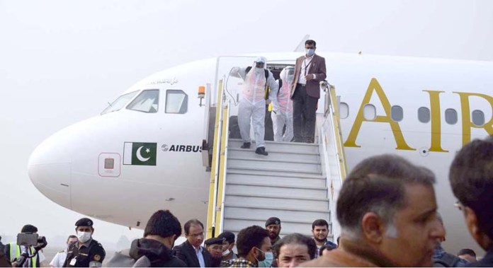 Staffers spraying anti COVID-19 fumigation during Air Sial arrival flight from USA at Sialkot International Air Port