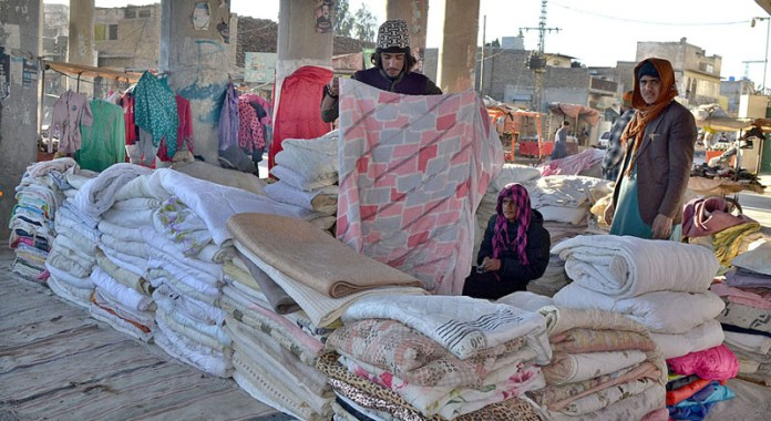 A vendor displaying and arranging quilts to attract the customers under bridge of Jaint Road