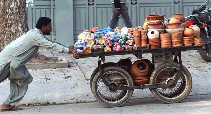 A street vendor pushing a hand cart loaded with clay made stuff to attract the customers