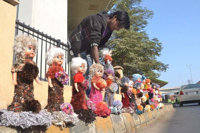 A vendor displaying and arranging plastic dolls to attract the customers at Chungi No.9