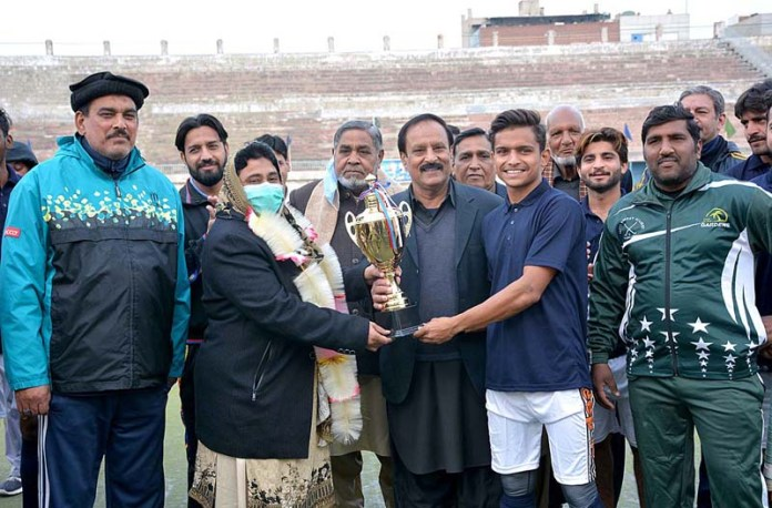 District Sports Officer Sajida Latif giving winning trophy to the Faisalabad Hockey team during prize distribution ceremony of Inter District Hockey Championship 2020 at Hockey Stadium organized by Sports Department