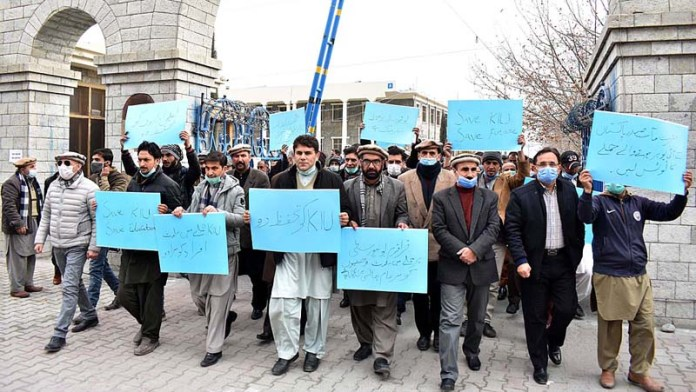 Teachers and students participating in a protest demonstration against the burning the under construction building of Engineering Karakoram International University and vehicles by unknown miscreants
