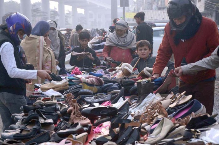 Ladies busy in selecting and purchasing footwear from roadside vendor