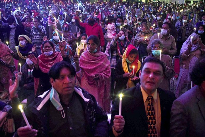 Christians attending candle light ceremony to mark Christmas celebrations outside a church