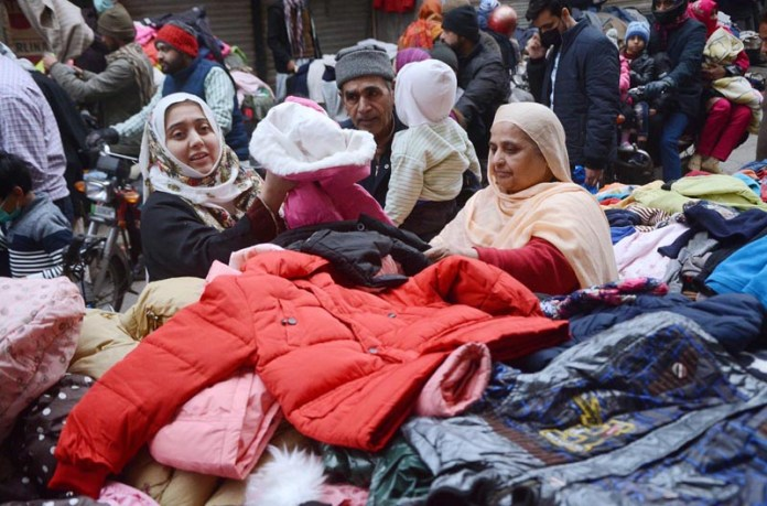 People busy in selecting and purchasing second hand warm clothes from roadside vendor