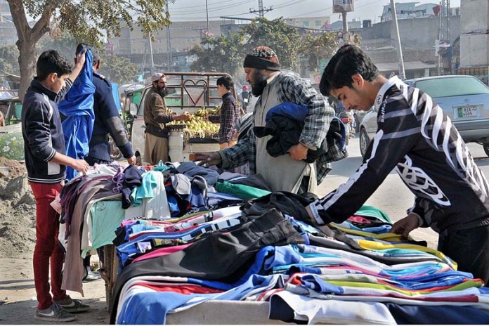 People busy in selecting and purchasing secondhand warm clothes from roadside vendor