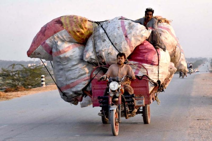 A view of overloaded motorcycle rickshaw on the way at Bypass Road