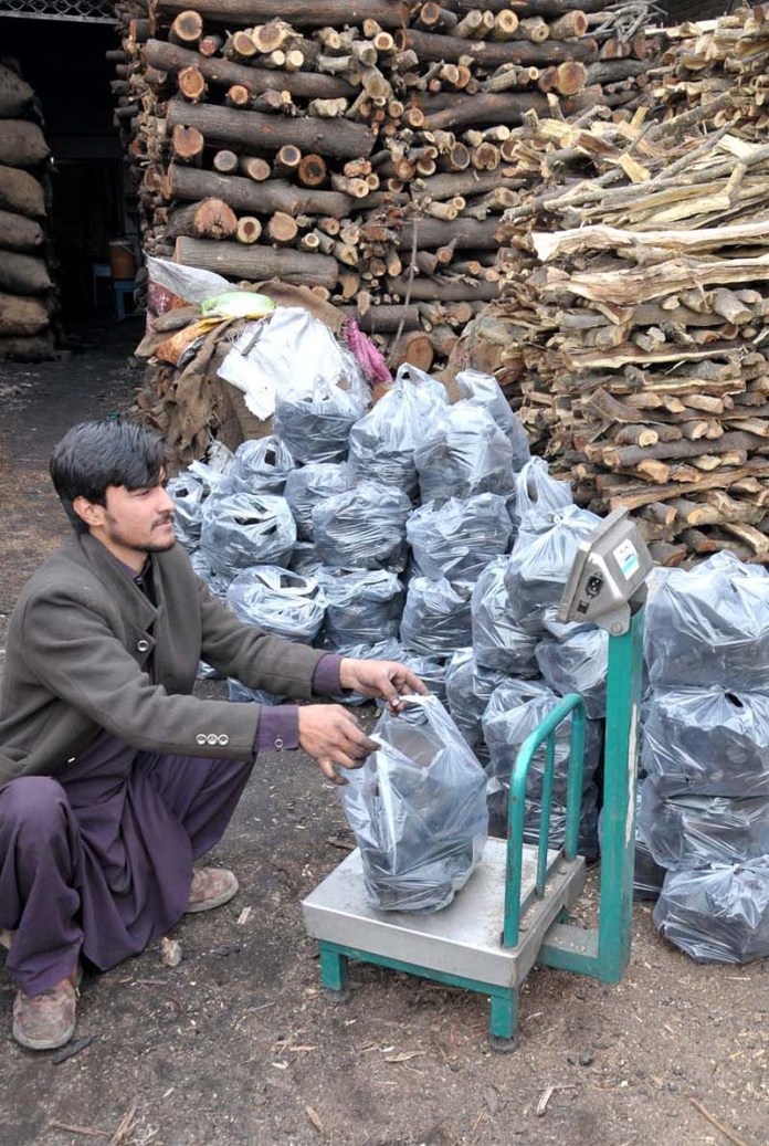 A vendor displaying weighing coal for customers at his stall