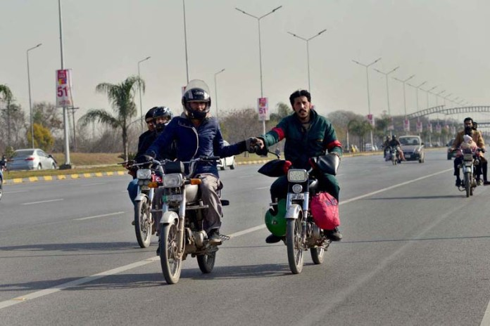 A motorcyclist giving helping hand to other one on Islamabad Express Way near Zero Point