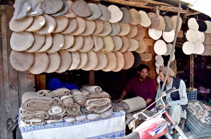 A vendor displaying traditional woolen caps to attract costumer at his work place near old bridge Konodas