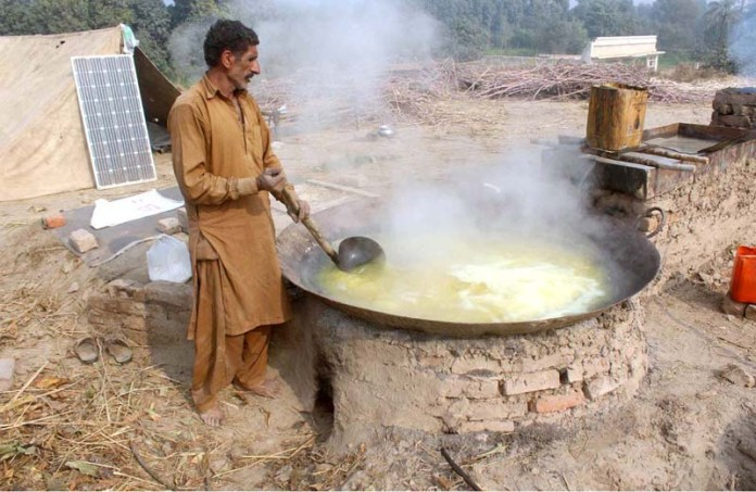 A farmer busy in boiling sugarcane juice to prepare sweet (Gurr) at his workplace