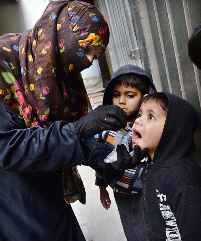 Health worker administering dose of vitamin to children at Samanabad during anti-polio campaign in Provincial Capital