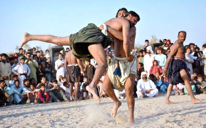 Wrestlers in action during traditional wrestling (Mulakhara) in front of Peer Ali Muhammad Shah Kaheri Shrine during annual urs celebrations at Right Bank of Indus River near Aqil Village