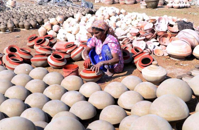 A woman worker busy in coloring the clay made pots after preparing at his workplace