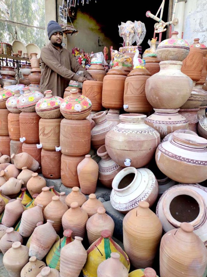 A vendor arranging and displaying clay made pots at his roadside setup