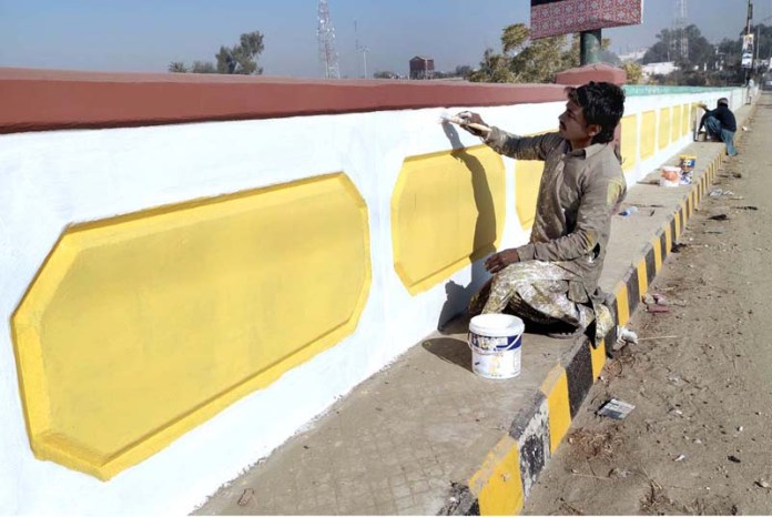Labourers busy in painting protective wall of railway head bridge during development work