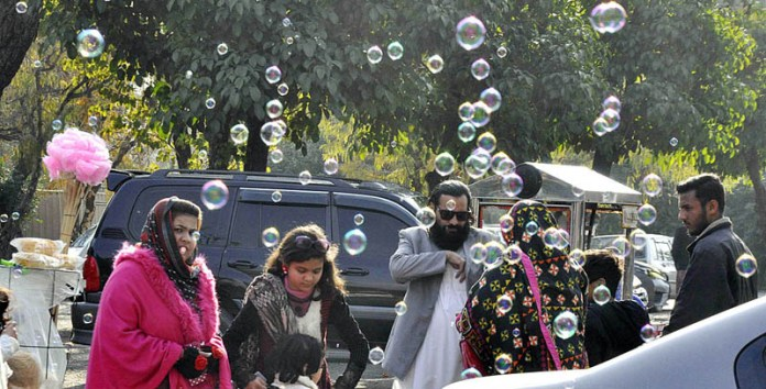 A vendor spreads water bubbles in air to attract the children at his roadside setup